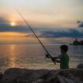 A young boy fishing in the setting sun at Piran Slovenia